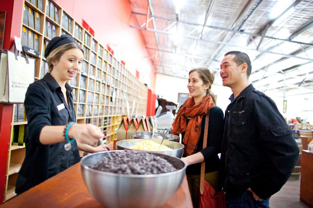 Customers enjoy a free sample from friendly employee at Margaret River Chocolate Factory in Western Australia