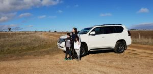 Mum and kids lean on white 4-wheel-drive in Snowy Mountains