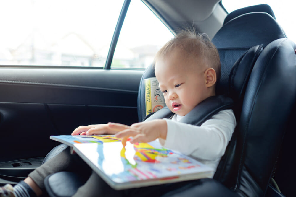 Baby reads a book in the back seat of a car