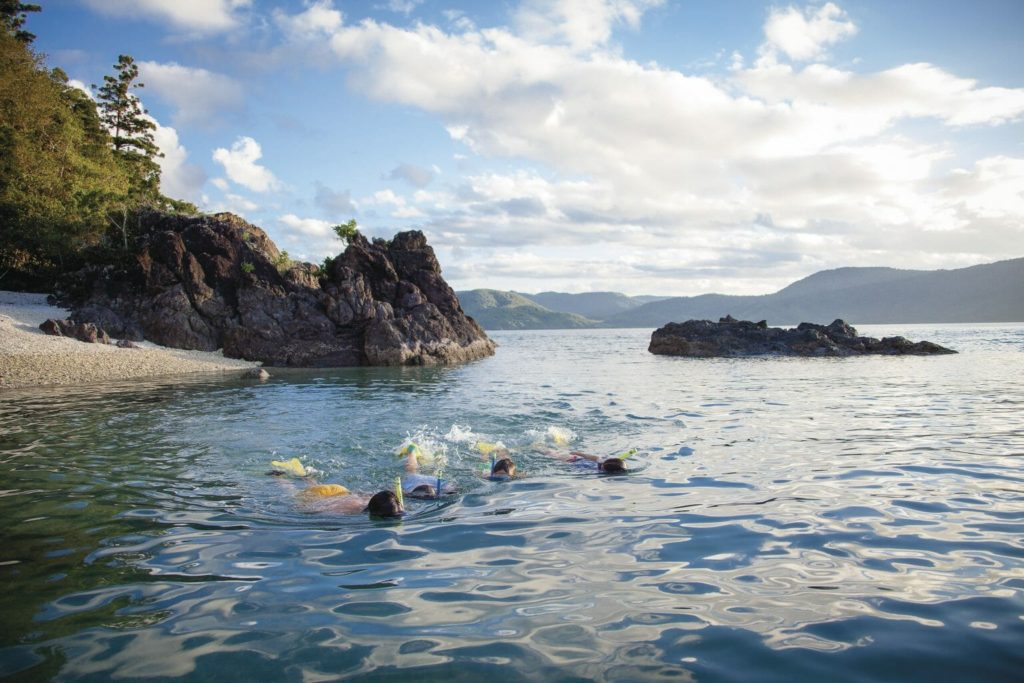 People snorkel in secluded cove