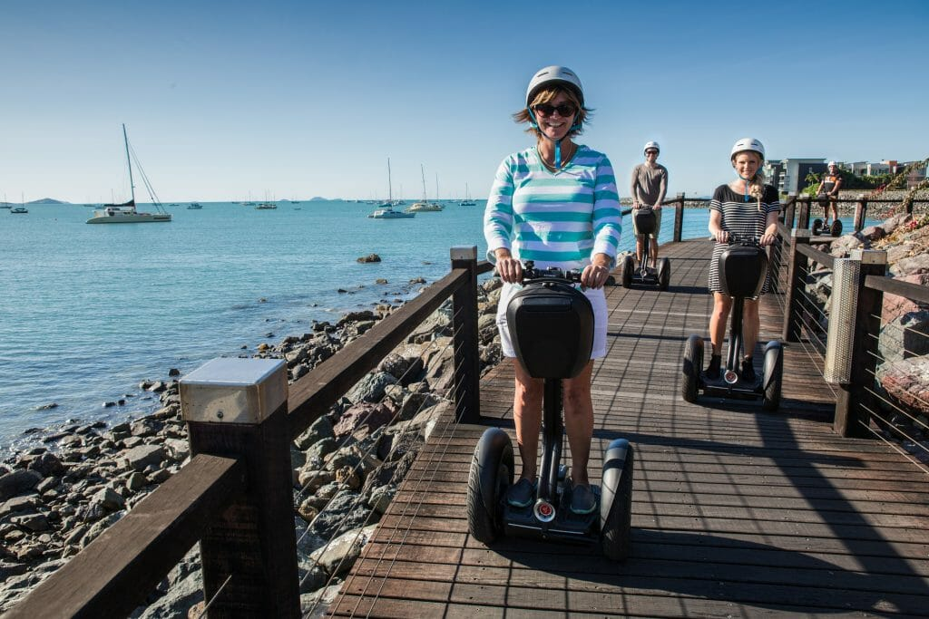 Family on segways along a seaside boardwalk at Airlie Beach
