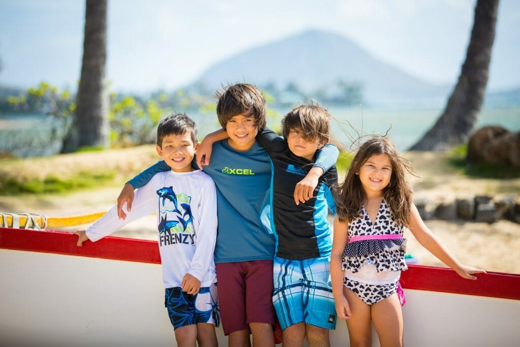 Kids smiling for photo with arms linked at Kahala Beach