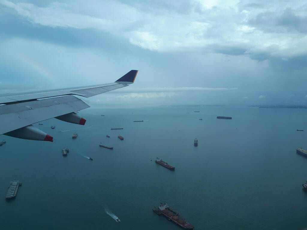 View of boats on ocean through plane window