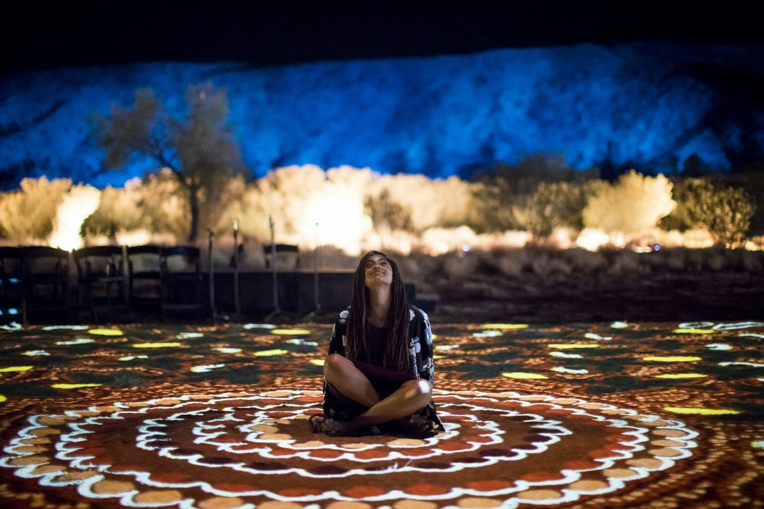 Girl sits on large-scale indigenous artwork at Alice Springs
