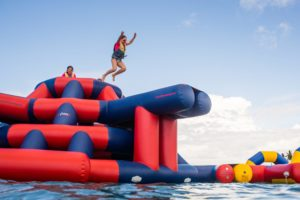 A child jumps off inflatable water park