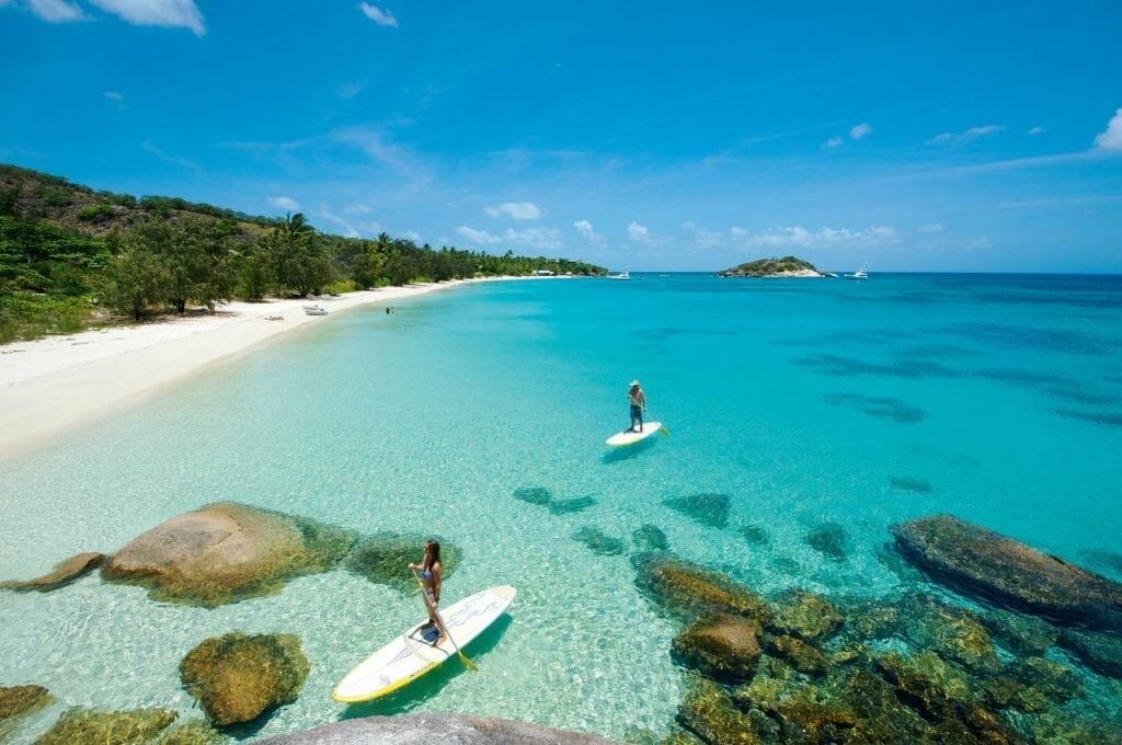 Two paddle boarders in crystal clear blue waters at Lizard Island all-inclusive resort