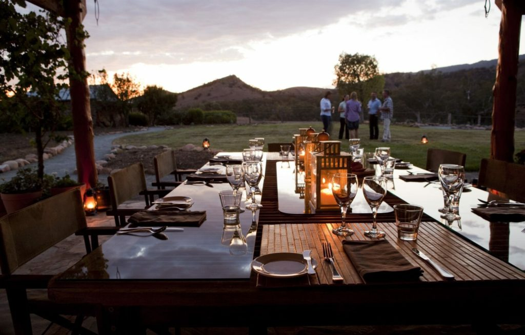 Dinner table set up at sunset with people standing in background drinking wine