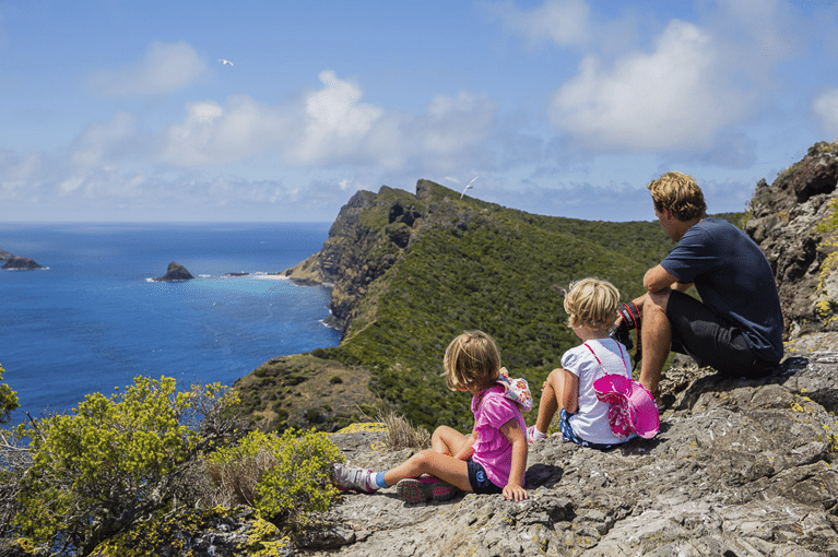 Two kids and father sit on edge of cliff overlooking water