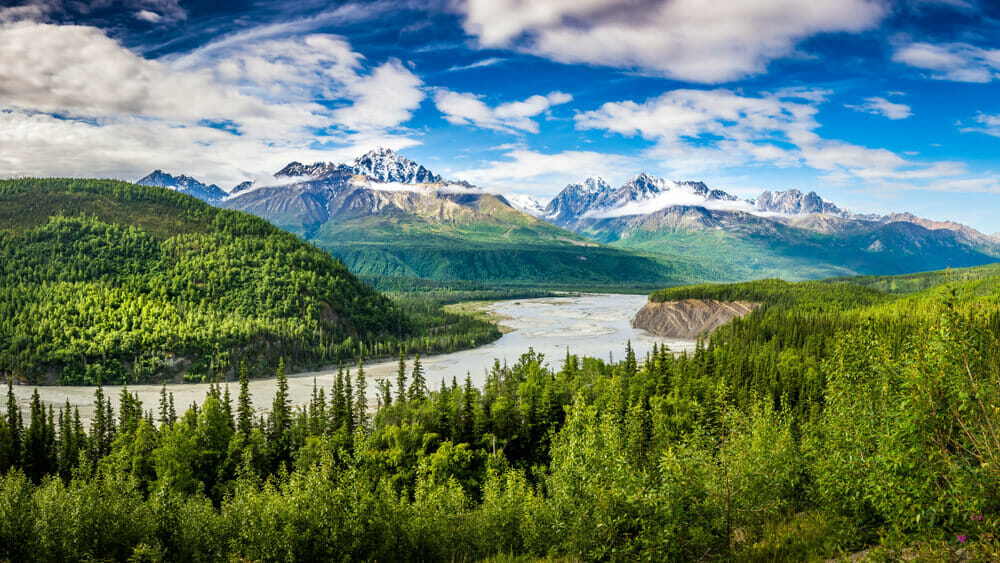 scenery shot: Snow-capped mountain, green trees and blue lake
