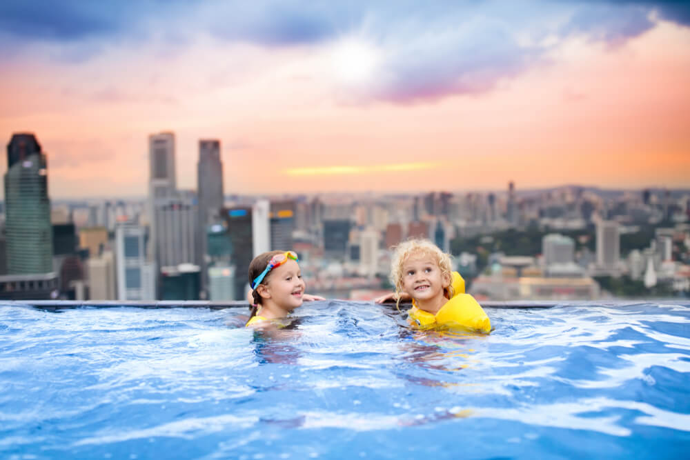 Kids swimming in rooftop infinity pool in Singapore