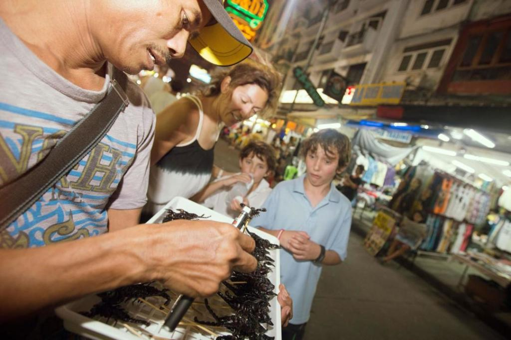 Kids trying scorpions on G Adventures family tour