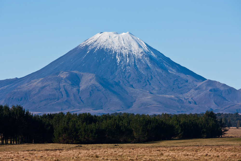 The top of the Mount Doom / Ngauruhoe covered in snow overlooking fields and trees in the North Island in New Zealand