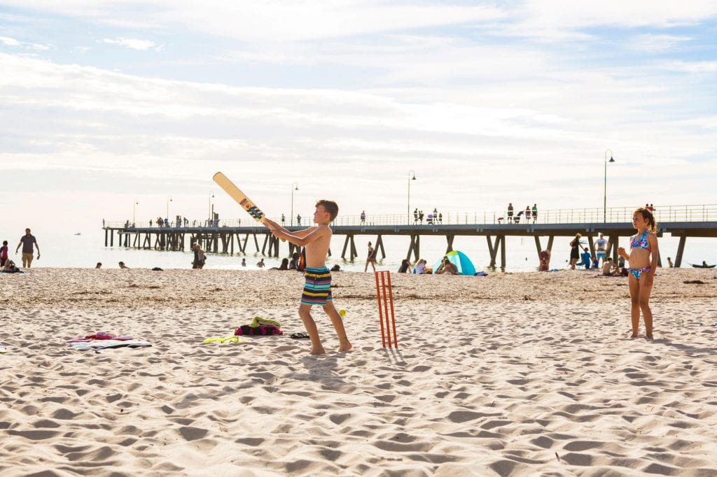 The wide sand of Glenelg is perfect for a hit of cricket. Credit: South Australian Tourism Commission/ Andre Castelluci