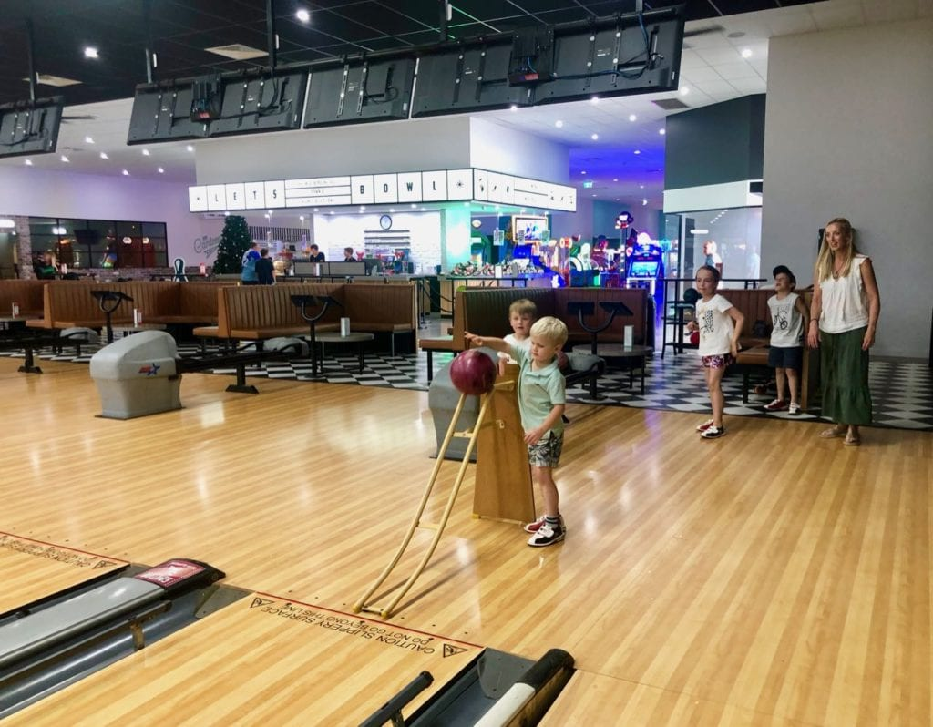 a young boy trying ten pin bowling for the first time