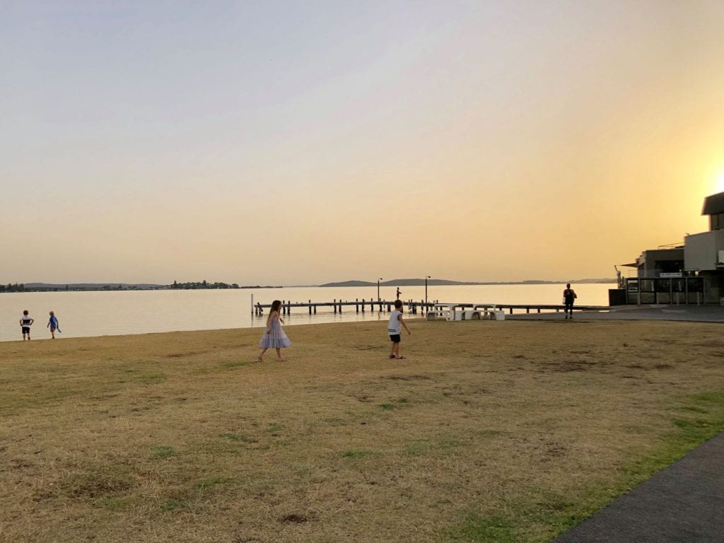 young kids running on the grass as the sun sets over Lake Macquarie