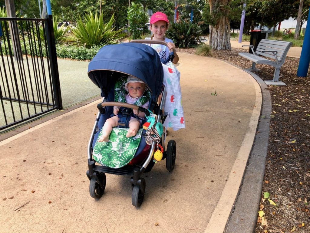 a young girl pushing a baby in a pram at Speers Point Park, Lake Macquarie.
