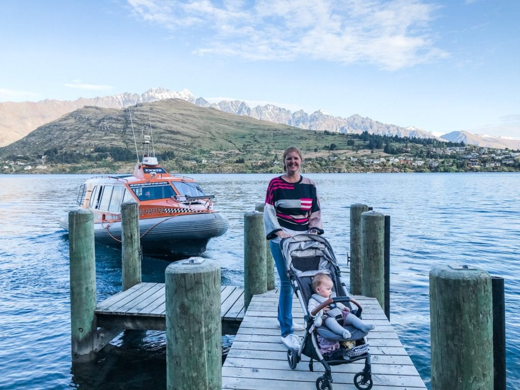 lady with a baby in a pram on a jetty waiting for a water taxi on lake wakatipu, Queenstown, New Zealand
