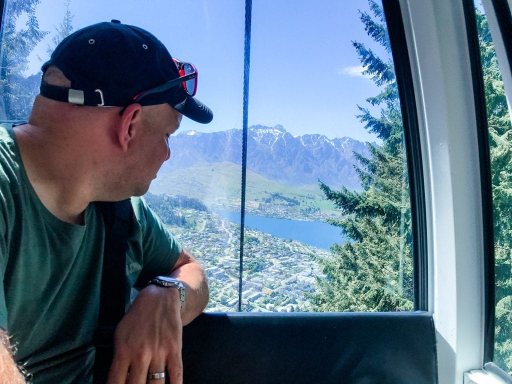 man in the skyline gondola looking at the view of Queenstown, New Zealand