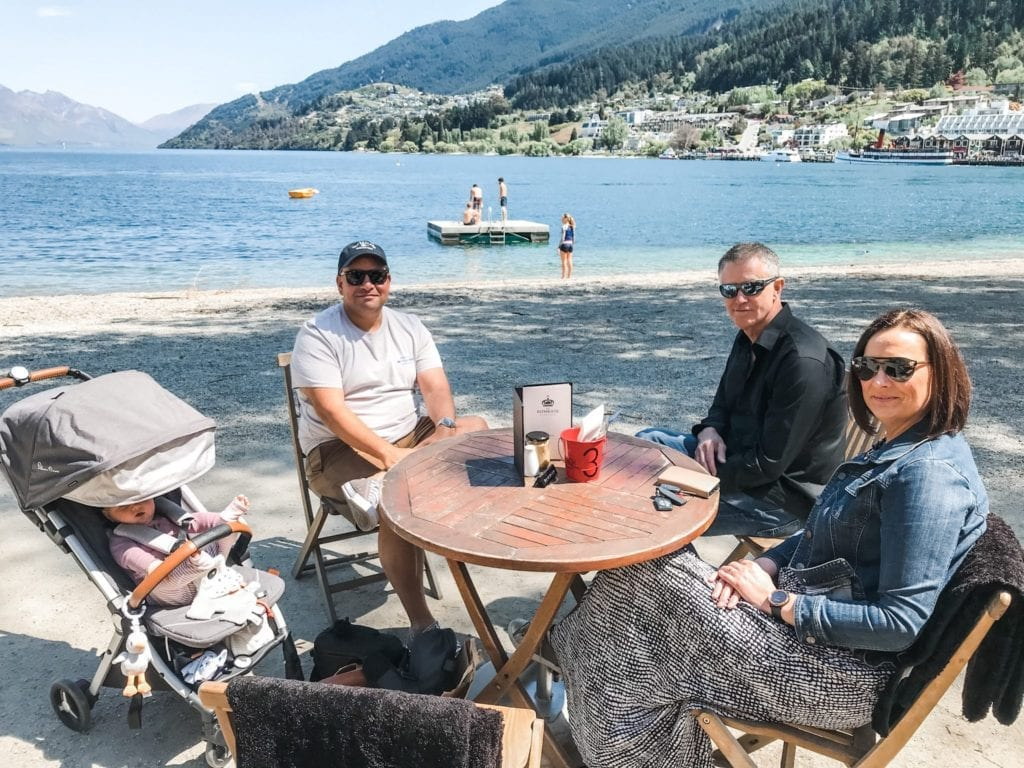 A small group of adults and a baby in a pram at an outdoor table at The Bathhouse Cafe Queenstown