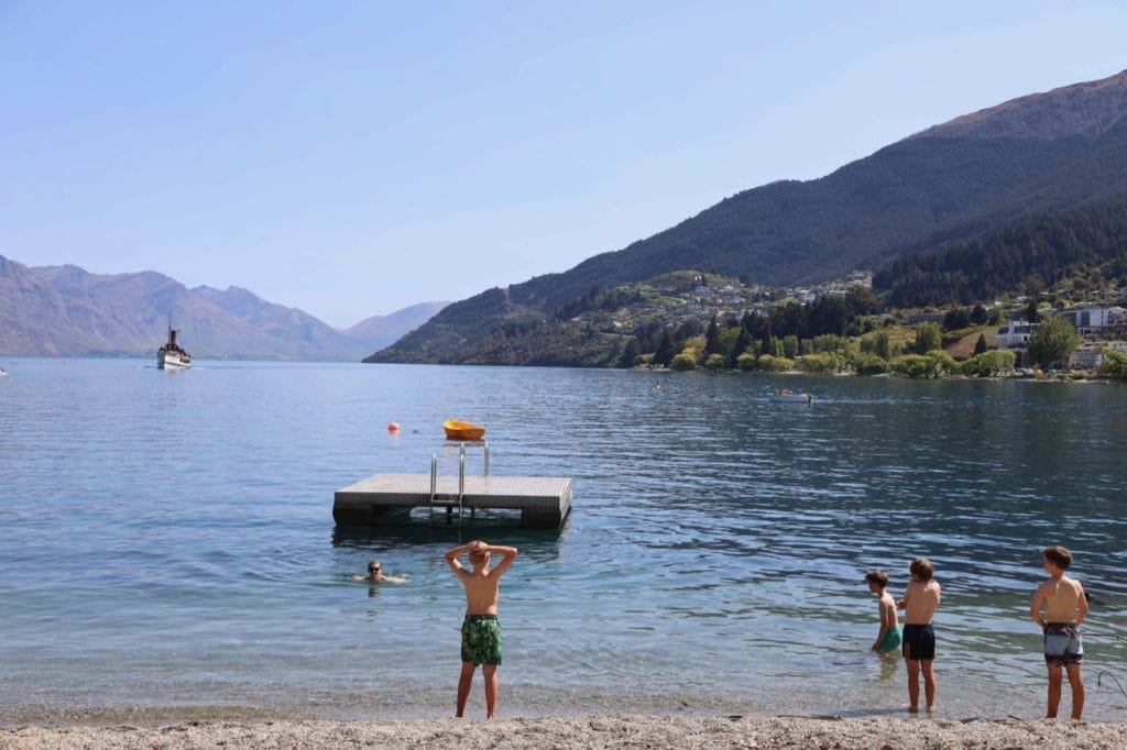 TSS Earnslaw in the background as young boys decide if they want to swim out to the pontoon from Queenstown beach