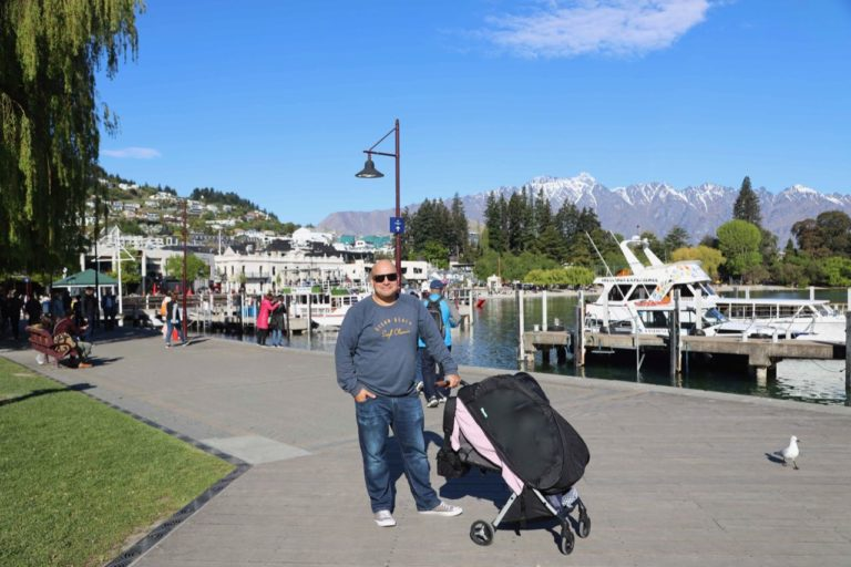 man with a baby in a pram in Queenstwon, New Zealand