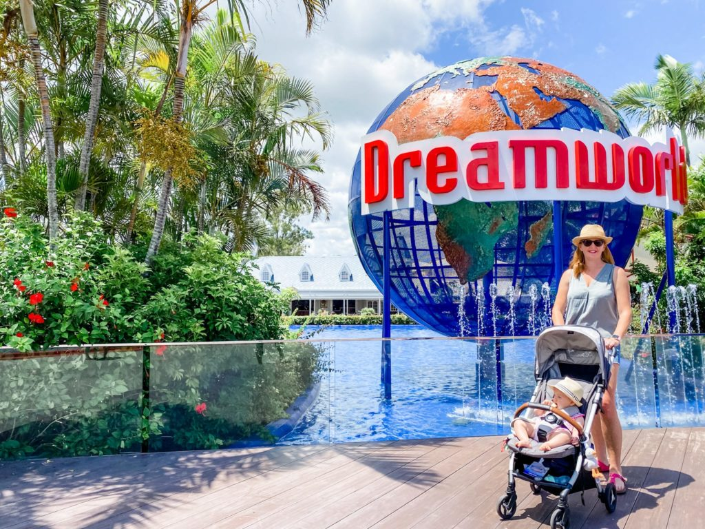 mother with baby in a pram in front of the Dreamworld globe at Dreamworld on the Gold Coast