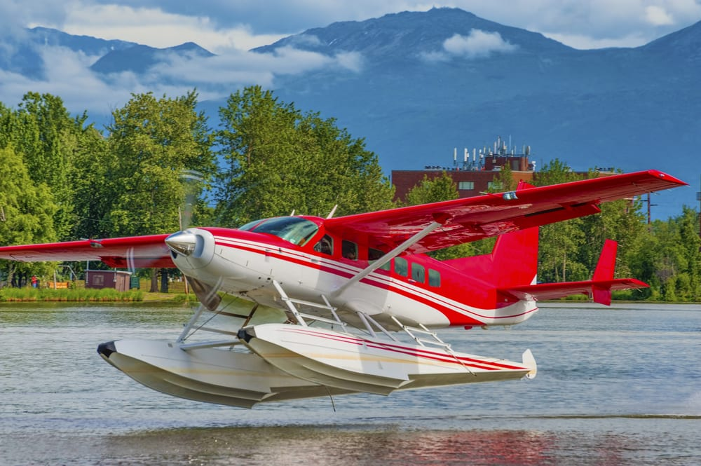 A red and white seaplane takes off on Lake Hood in Anchorage Alaska