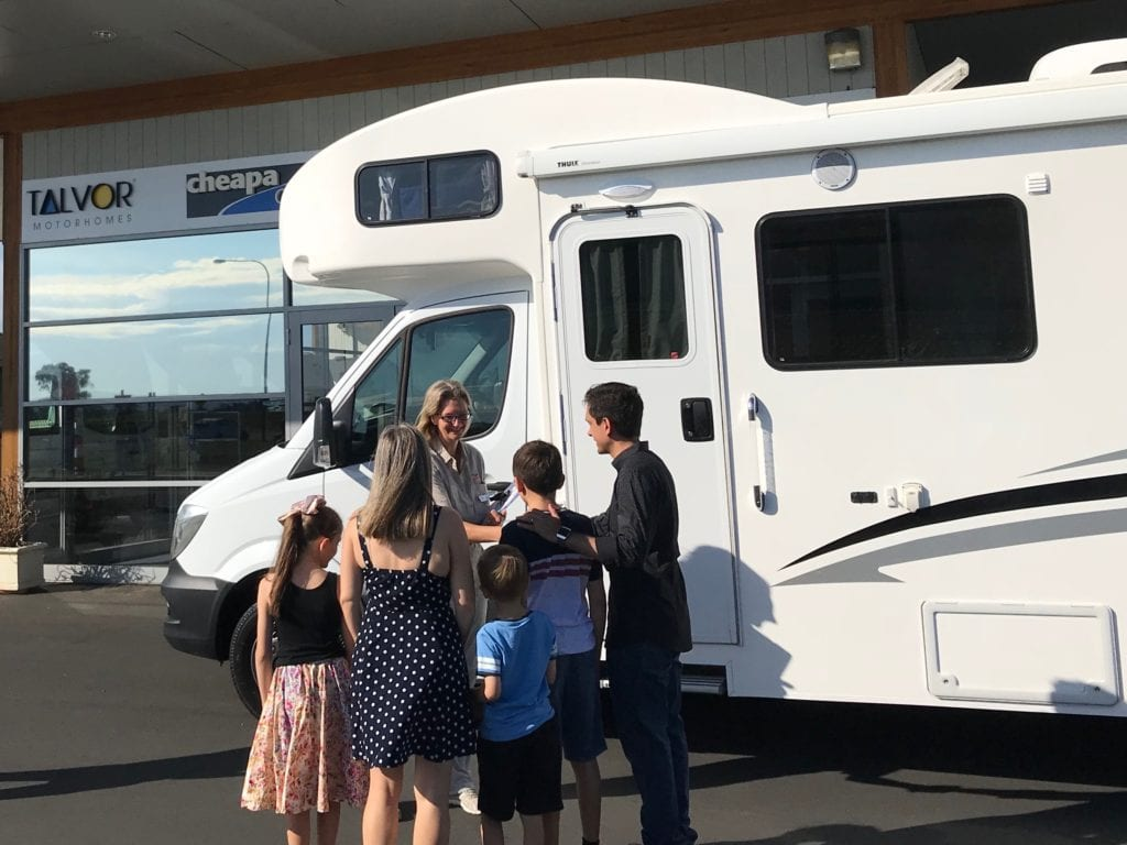 family collecting the keys to an Apollo motorhome