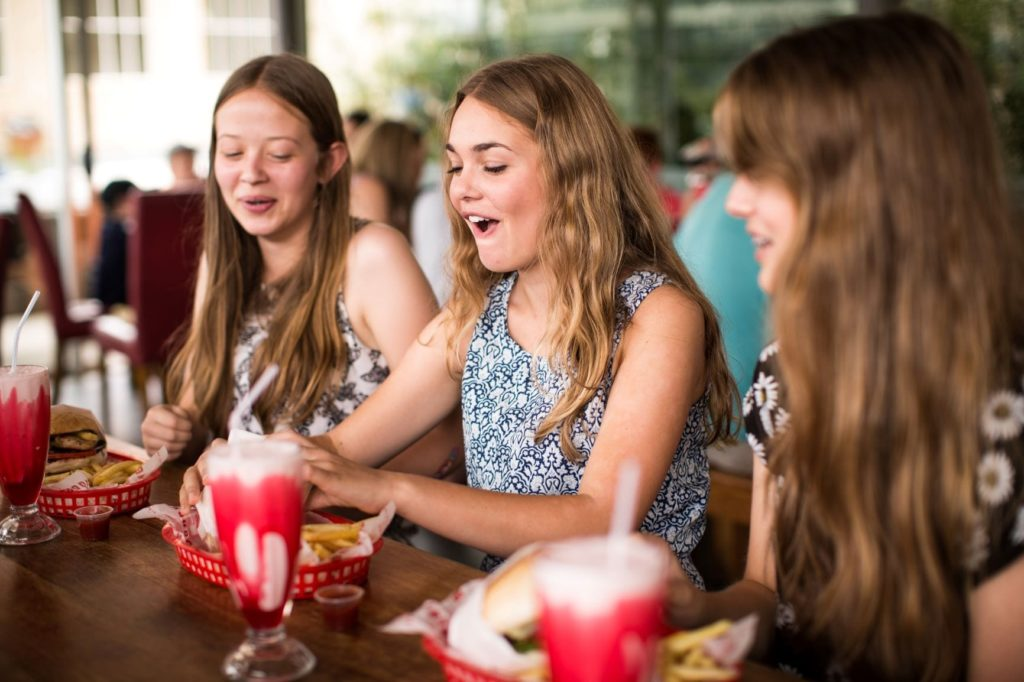 Teenagers eating delicious burgers and shakes at Brodburger in Canberra