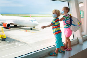 afe travel with young child and baby. Kids boarding airplane in surgical masks.