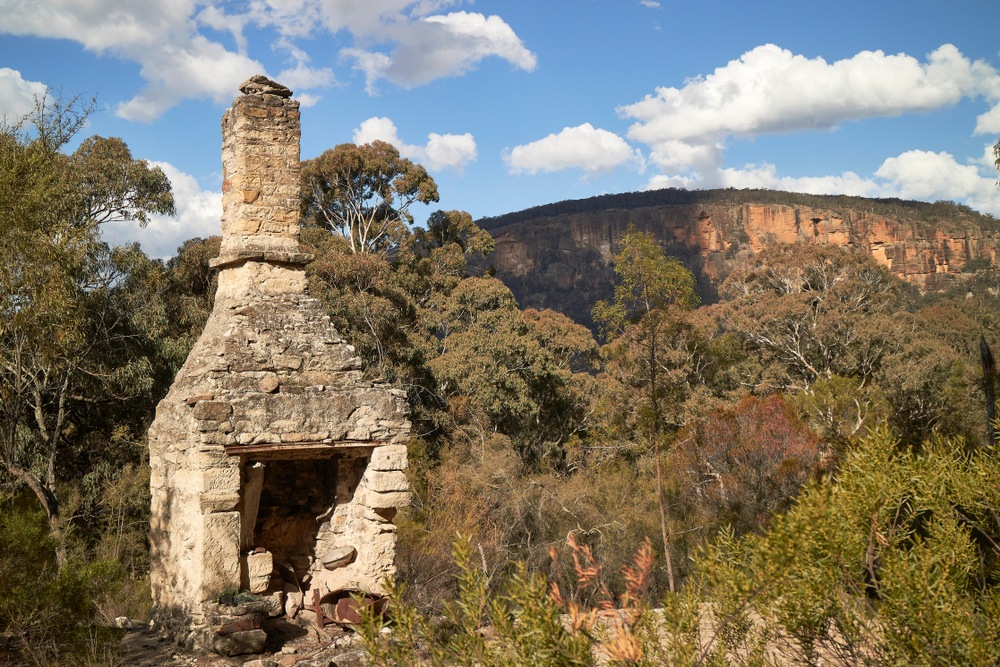chimney ruin in front of mountain escarpment in Capertee National Park