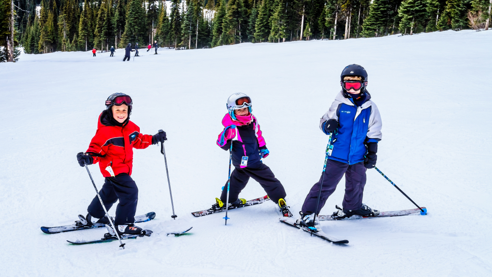Kids on skis having fun on a white Christmas holiday at Sun Peaks in British Columbia