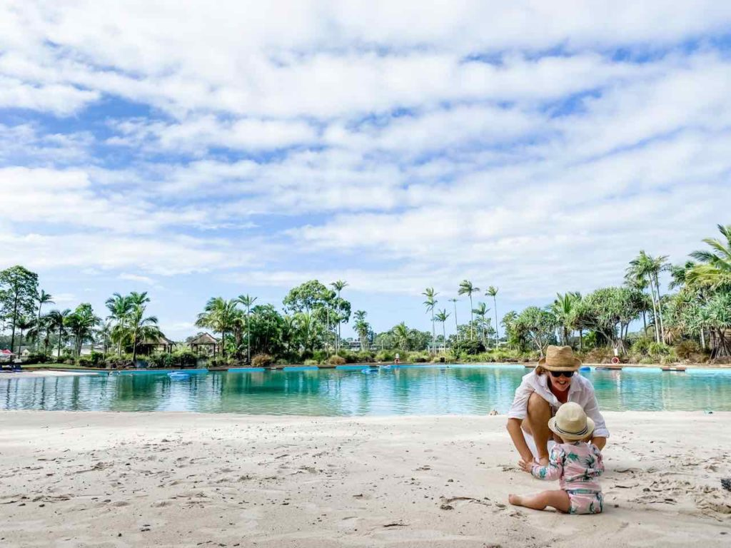 mother and small child on the edge of the lagoon beach pool, one of Australia's best hotel pools, at the Intercontinental Sanctuary Cove