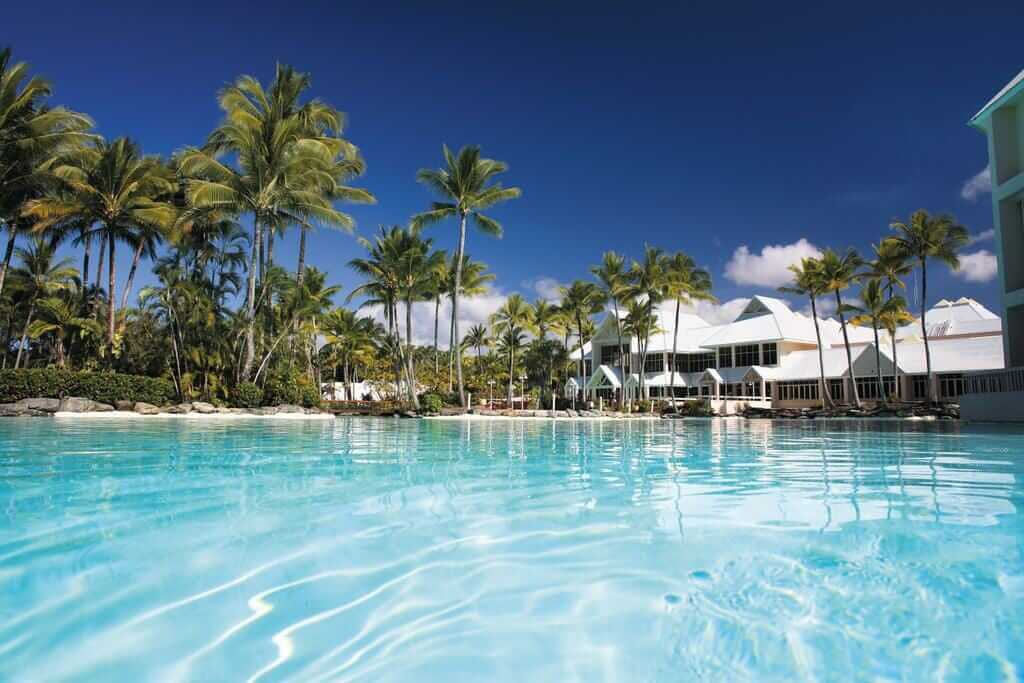 hotel pool fringed by palm trees at the Sheraton Grand Mirage in Port Douglas