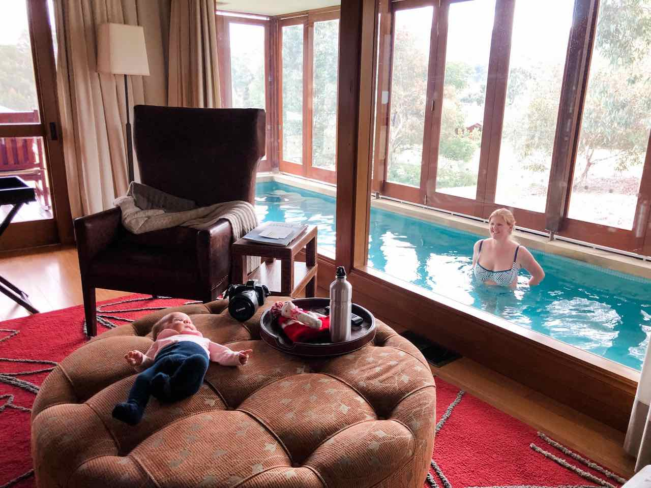 baby lying on an ottoman in the room at Emirates One & Only Wolgan Valley, while mum is in the in-room pool looking on