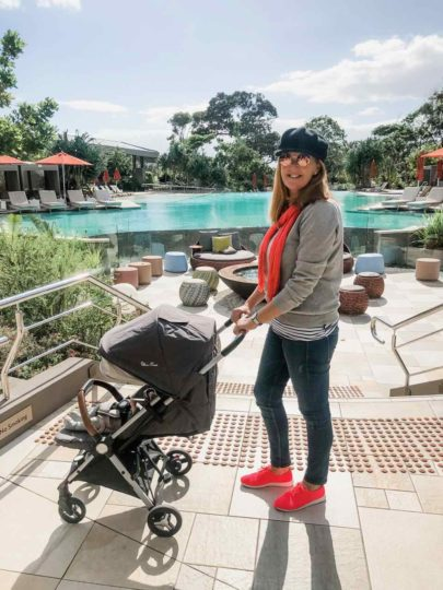 mother and baby in a pram in front of the main pool at Elements of Byron in Byron Bay