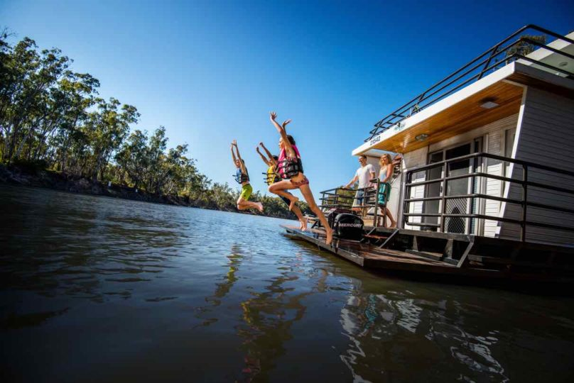 kids jumping off the back of a houseboat in life vests as the parents watch. Part of a houseboat family holiday on the Murray River