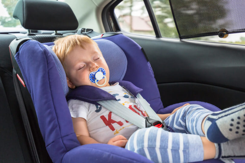 little boy with red hair sleeping in his car seat