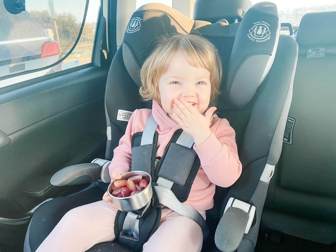 little girl in a pink tracksuit eating grapes while sitting in her car seat in the back of a car
