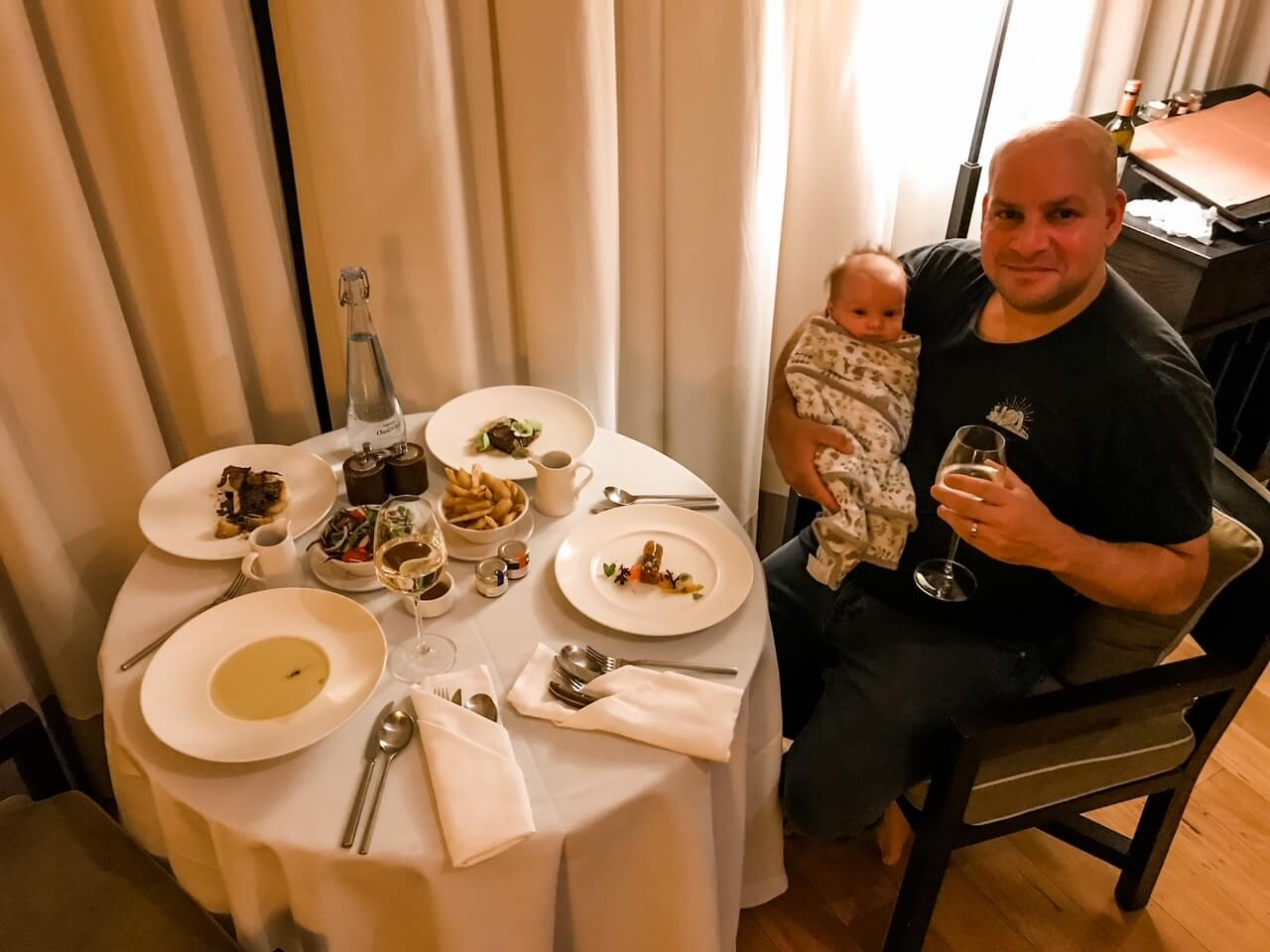 man holding a glass of wine and a tiny baby having in room dining at Emirates One&Only Wolgan Vally